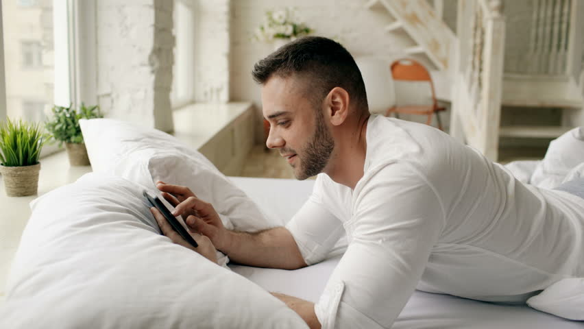 Young attractive man using tablet computer lying in bed while his girlfriend come and hug him in bedroom at the morning | Shutterstock HD Video #26721040
