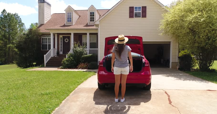 Drone footage 4K 60 fps.Young woman in hat takes groceries from trunk and comes to house.Girl after shopping in store returning home and goes out red car.Suburb building located in green subdivision