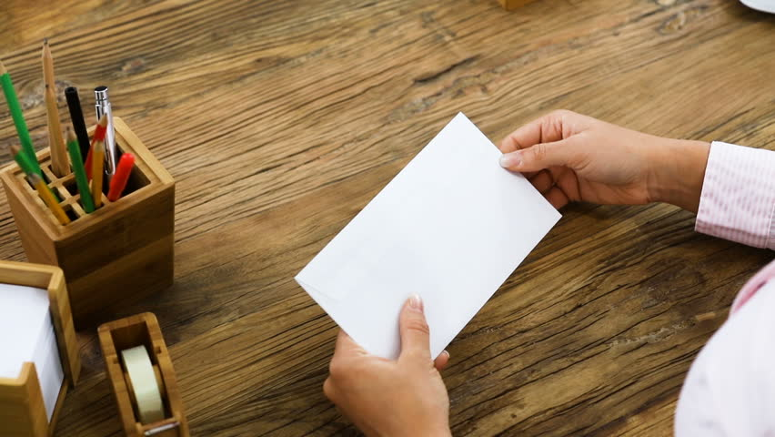 Elevated View Of A Businessperson Opening An Invoice From White Envelope On Office Desk