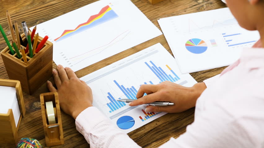 Close-up Of A Businesswoman Analyzing A Colorful Fluctuating Bar Graph On Desk In Office | Shutterstock HD Video #26745460