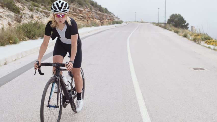 Cute petite girl bicycle rider climbs a steep uphill in the clouds on top of the mountain alone trying to beat her record and fight herself, her jersey opens in strong wind
