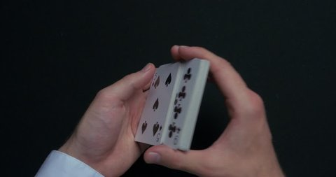 Poker game - shuffling cards. Man's hands shuffing cards. Close up. Man's hands shuffling playing cards. Dealer's hands shuffling cards during a poker game