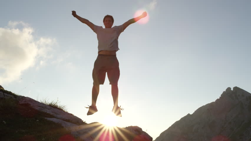 CLOSE UP, SLOW MOTION: Cheerful hiker standing on the edge of steep rocky mountain jumping with hands raised celebrating success. Happy man jumping for joy on the peak of the mountain after long walk