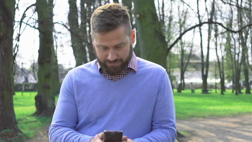 Man in park, browsing smartphone, portrait steadicam shot #26821180