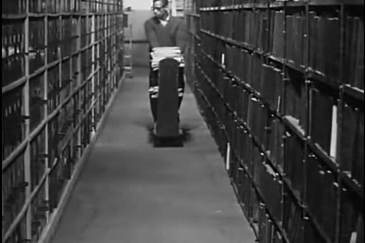 1960s: Long rows of medical texts are shown in the National Library of Medicine, as a narrator explains how acquisitions and cataloguing have changed from the 1800s to 1963.