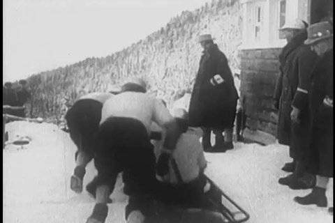 1930s: Crews race bobsleds down an ice track and crash, repeatedly, in the snow, in 1938.