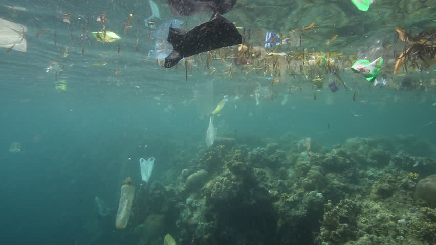 Plastic garbage and other trash floating underwater over fragile coral reef
