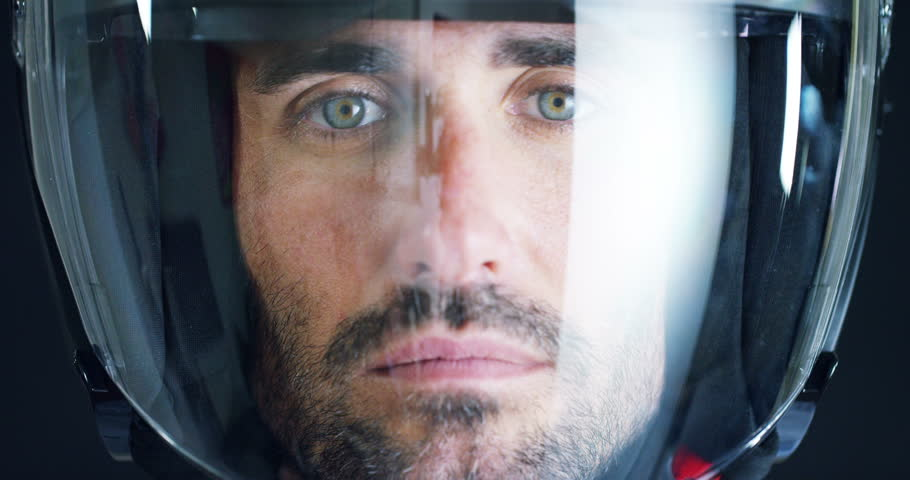 Portrait of a professional rider or motorcyclist, in a protective black helmet, on a black background. Concept: driver, drive, speed, defense, space, airplane, pilot, protective suit, extreme, sports.