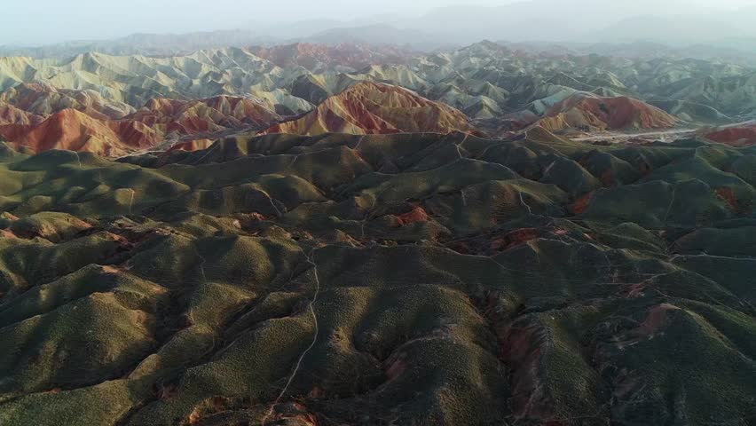 Approaching beautiful rainbow mountains in Zhangye National Geopark, part 2 of a continuous 3 part series. Aerial view on an orange sandstone mountain chain surrounded by green vegetation.