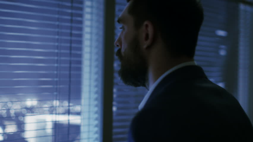 Late at Night Businessman Looks Through Window Blinds and Looks on Big City with Skyscrapers.  | Shutterstock HD Video #26897050