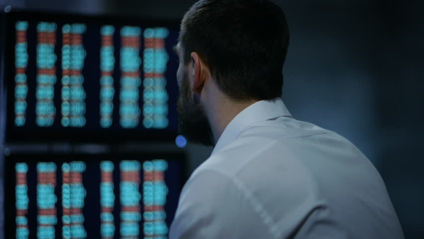 Late at Night Trader Reads Numbers on His Multiple Displays with Stock Information on Them. In Background Big City Window View. Shot on RED EPIC-W 8K Helium Cinema Camera. | Shutterstock HD Video #26897080