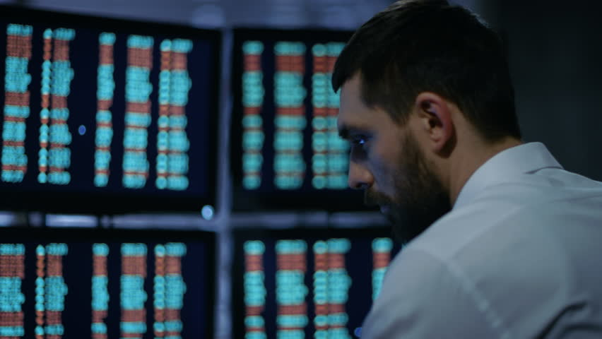 Late at Night Trader Reads Numbers on His Multiple Displays with Stock Information on Them. In Background Big City Window View. Shot on RED EPIC-W 8K Helium Cinema Camera.