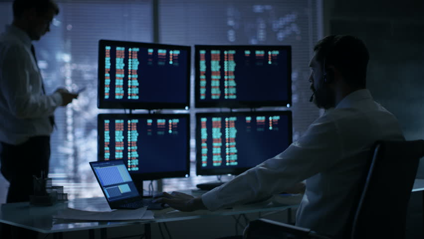 Late at Night in Trader's Bureau. Stockbroker Reads Numbers on His Multiple Displays with Stock Information on Them,He Also Consults Clients with Headset On. | Shutterstock HD Video #26897146