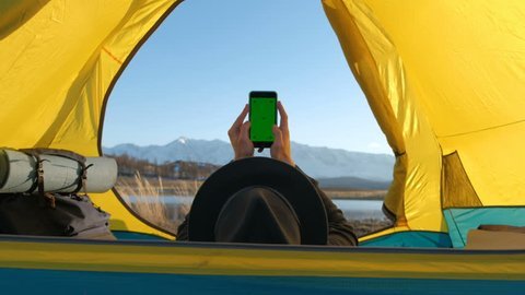 The solar panel attached to the tent. The man sitting next to mobile phone charges from the sun 20s 4k