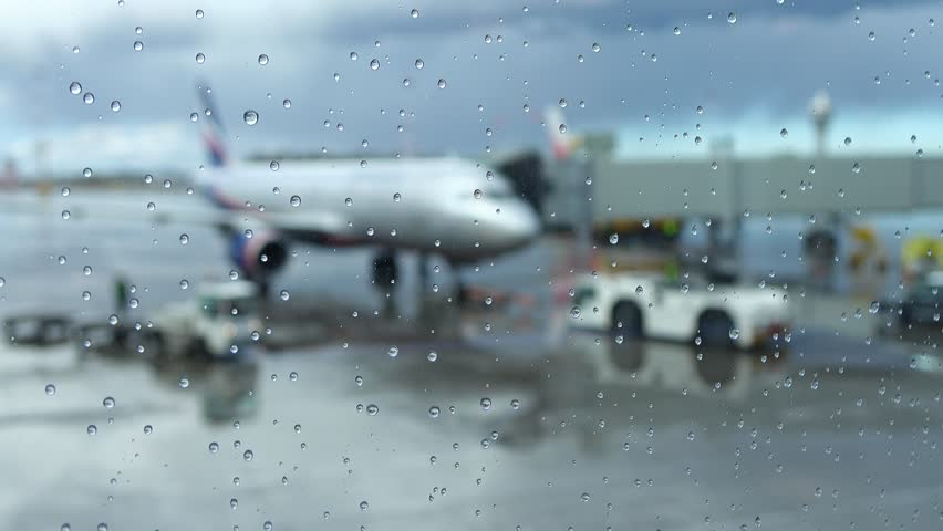 Blurred view of passenger airliner prepared to departure, stand with passengers on board. Rainy weather, focus on nice rain drops on glass, view from terminal lounge. Air transportation concept