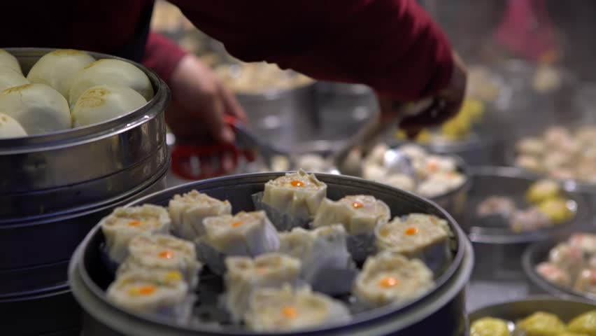 4K Vendor preparing and selling Shaomai and customers at Asian Street Food Market in Taiwan. Dumpling is a chinese traditional food at Oriental Night Market. Restaurant in downtown-Dan