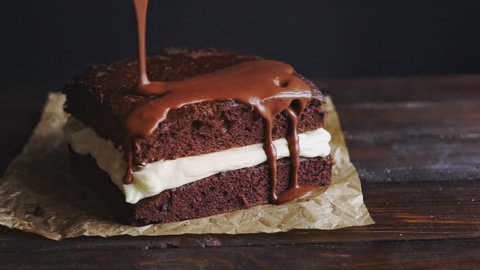 Chocolate icing on cake. Chocolate glaze pouring on homemade dessert. Close up of biscuit cake decoration. Topping chocolate dessert