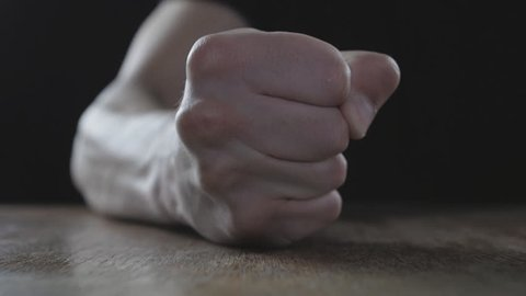 Fist of angry man beats on the table in slow motion