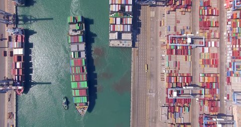Commercial port with container ships during loading and unloading, and a container ship pulled by tugboats - Top down aerial view.