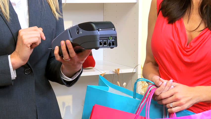 Customer in close up paying by credit card in fashionable boutique