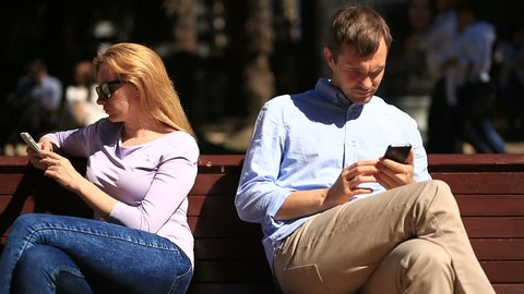 Man and woman looking in different directions, sitting on a bench looking at mobile phones