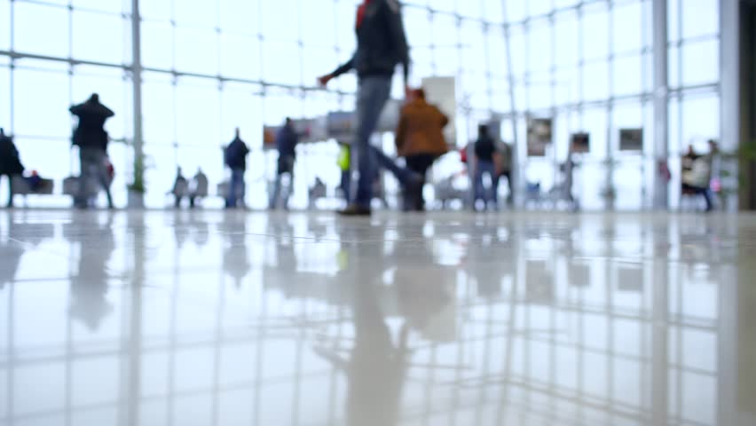 People out of focus walk inside a bright, modern building. Focus in the foreground | Shutterstock HD Video #27028060