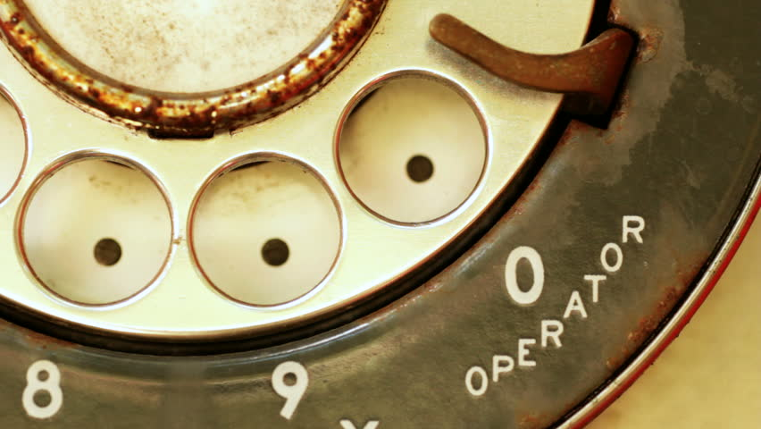 Extreme close-up of a finger dialing an old rotary pay phone.