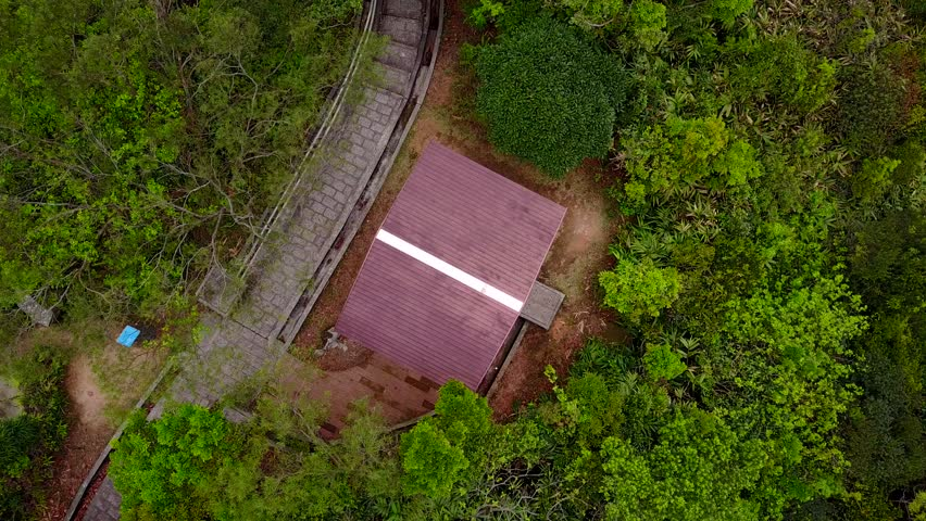 Small modern pavilion roof in green country park, stony path beside structure. Aerial spin upwards shot, camera look straight down from top point and slowly rotate around vertical axis | Shutterstock HD Video #27042940