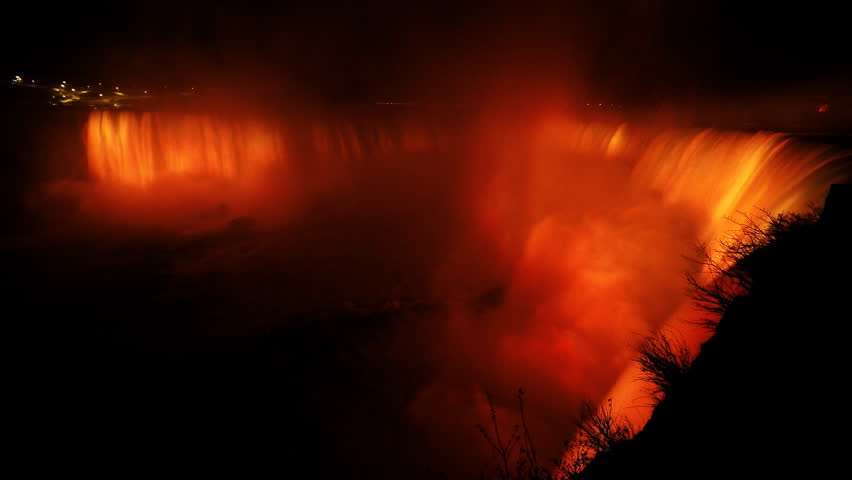 Niagara Falls bursting with rising water and mist illuminated by multi-colored energy saving LED lights at night