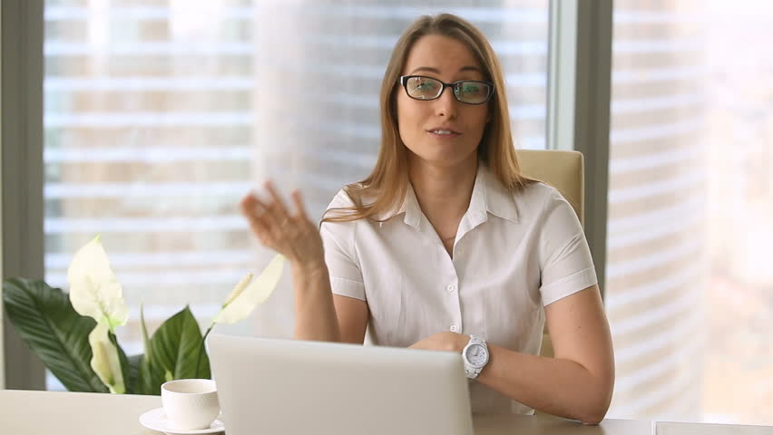 Smiling young confident businesswoman in glasses looking at camera, sitting at office desk, talking. Call, promotion, video blogging, online webinar training, educational vlog, how to start business