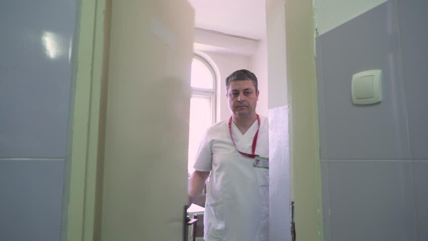 Medical technician in white uniform comes through the door and taken blood bags from the fridge and adds nurse, concept blood transfusion, steady cam shot, tracking, interior scene