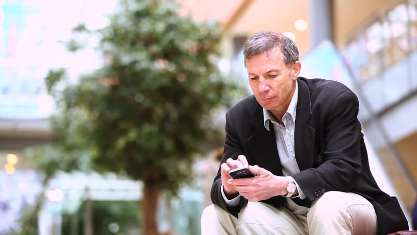 Businessman using smart phone in the city. Caucasian man on his late fifties, sitting on a bench and typing on his smart phone. Business and lifestyle concepts. | Shutterstock HD Video #27063532