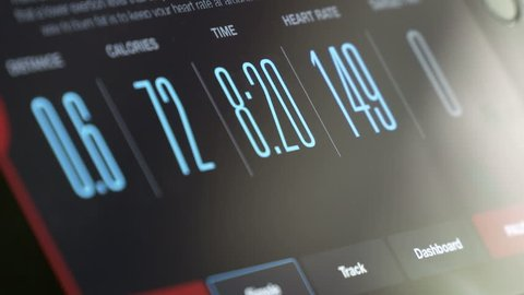 Fitness App displaying workout data on tablet screen time-lapse. Digital tablet linked with fitness machine displaying distance, burning calories, time and heart rate.