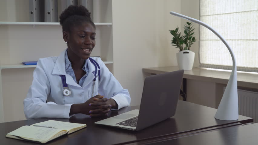 afro american doctor chatting online with client professional woman wearing in white coat on her - How To Get Hired After Being Fired Or In Downtimes