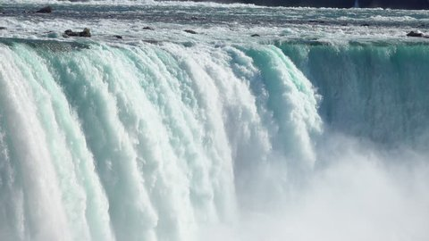 CLOSE UP Powerful raging whitewater waterfall falling forcefully over a rocky edge. Crystal clear glacier water stream dropping over the steep vertical cliff. Misty majestic Niagara Falls river rapids