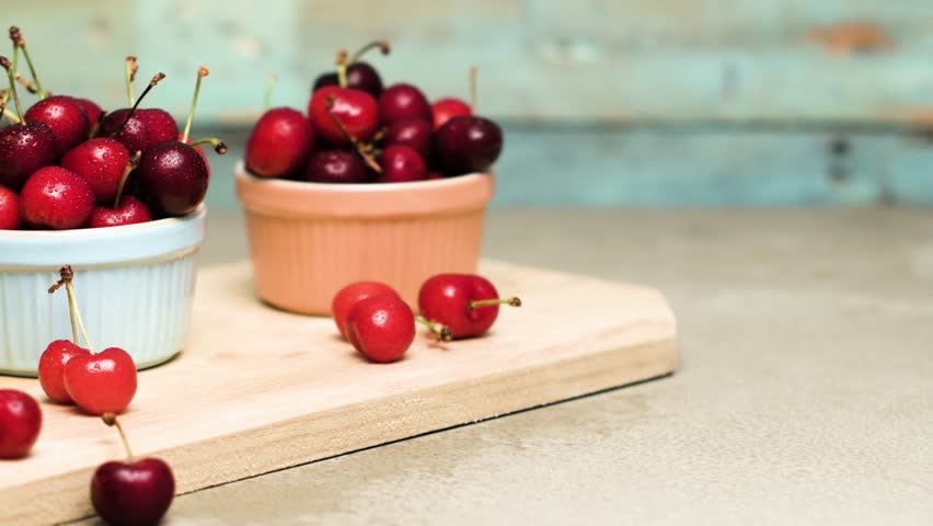 Red ripe cherries in ceramic bowls on kitchen countertop. Slide from left. #27121579