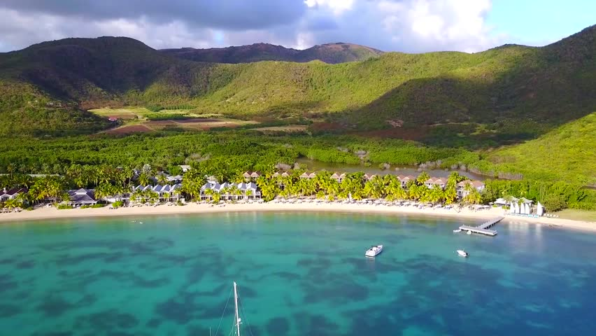 An Aerial video shot with a drone of some luxury resort and beach in Antigua, The Caribbean with blue water and mountains in the background on a sunny day with blue sky and sailboats in the sea