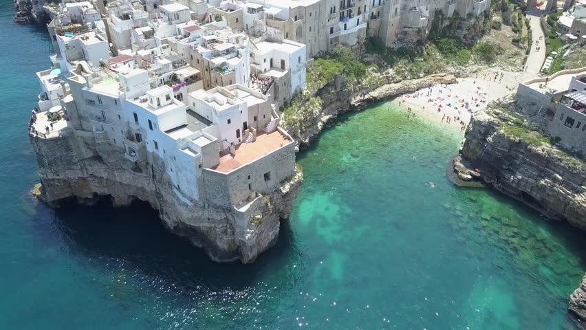 Polignano a Mare ( Bari , Italy ): heaven on earth. Coastal aerial 4k drone footage video above sea