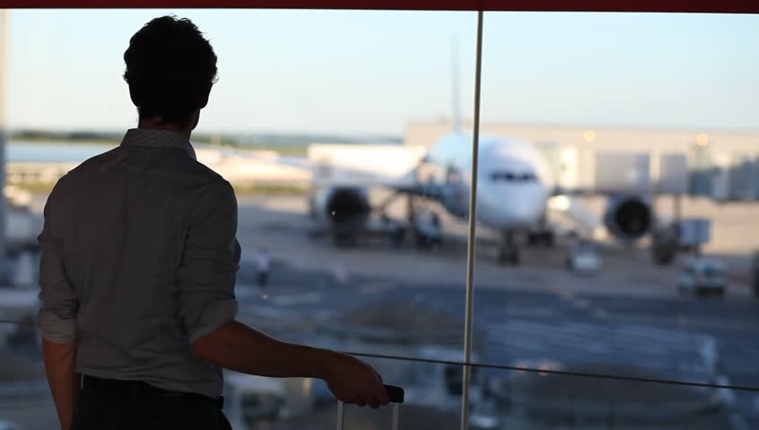 traveler waiting in airport, looking at window and using his smart phone, silhouette