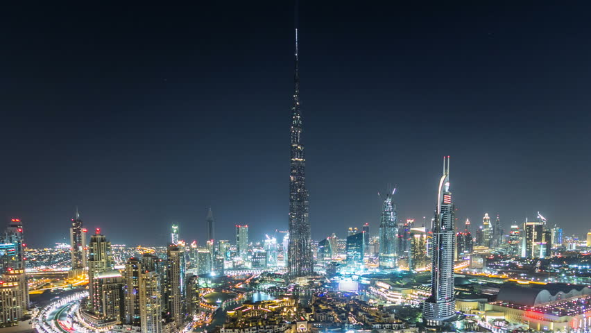 Dubai Downtown night timelapse with Burj Khalifa and other towers paniramic view from the top in Dubai, United Arab Emirates. Traffic on circle road and music fountain show. Pan down