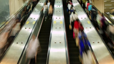 Hundreds of people zoom past on escalators. Time Lapse.