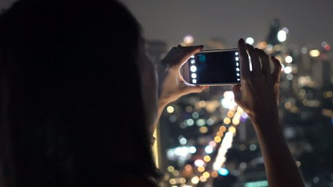 Woman taking photo of cityscape view with cellphone in bar at night