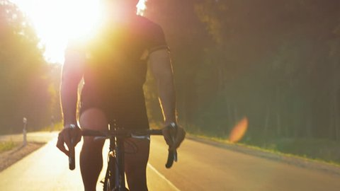 Person riding a bike down the road against the morning sun. Concept of persistence and the will to improve oneself. Never give up.