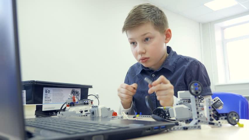 The portrait of the boy assembling the robot. Close-up. 4K. | Shutterstock HD Video #27197530