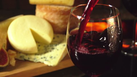 Close-up of a glass of red wine on a background of a cheese plate near the fireplace