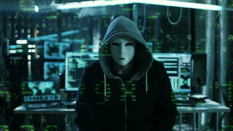 Dangerous Internationally Wanted Hacker with Masked Face Speaks into the Camera with Raining Numbers Video Effect. In the Background His Operating Room with Multiple Displays and Cables.RED Cinema UHD