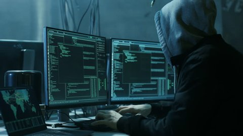 Dangerous Hooded Hacker Breaks into Government Data Servers and Infects Their System with a Virus. His Hideout Place has Dark Atmosphere, Multiple Displays, Cables Everywhere. Shot on RED Camera 4K.