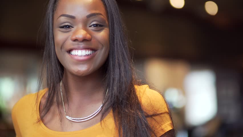 Portrait of a happy young attractive Black woman in 20's looking at the camera, smiling and laughing. Indoors, smart casual with blurred people in the background and shallow depth of field bokeh.