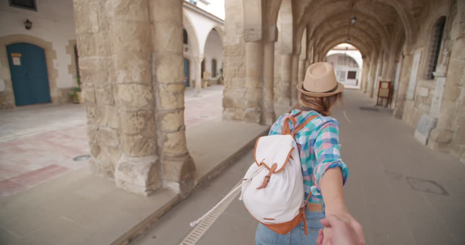 Woman tourist with map holding her friend's hand showing him the way around medieval town
