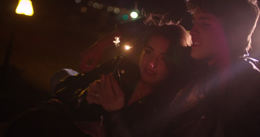 Teenage boy and girl with firework having a date in the city at night
